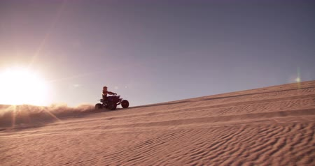 atv : Professional quad biker racing downhill over a sand dune in a desert race in Slow Motion Stock Footage