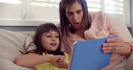 yapıştırma : Smiling mother and daughter sitting on a sofa playing together on a digital tablet  in Slow Motion Stok Video