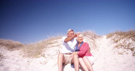 emekli : Happy retired couple enjoying some time together sitting on the sand at the beach in Slow Motion