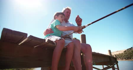 ryba : Retired grandfather sitting on a jetty teaching his grandson to fish Panning in Slow Motion