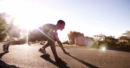 stanovena : Athlete preparing for a fitness run on a deserted road on a bright sunny morning slow motion