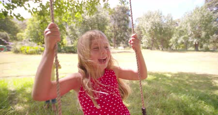 Child friends helping each other swing in a sunlit park