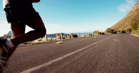 африканского происхождения : Closeup of running feet on mountain road in slow motion african american runner Стоковые видеозаписи