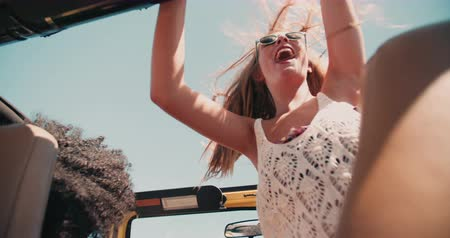 droga : Blonde teenage girl standing and waving happily in an open top vehicle on a road trip in Slow Motion Wideo