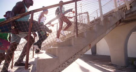 longboarder : Group of teenaged African American skater friends walking together in an urban setting in Slow Motion