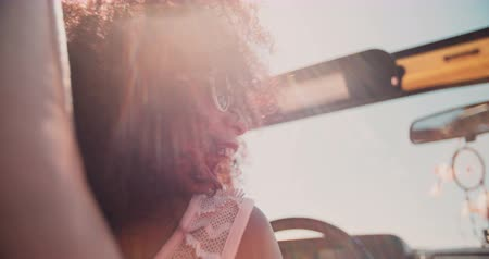 Smiling Afro girl driving in an open top vehicle while on a road trip for summer vacation in Slow Motion