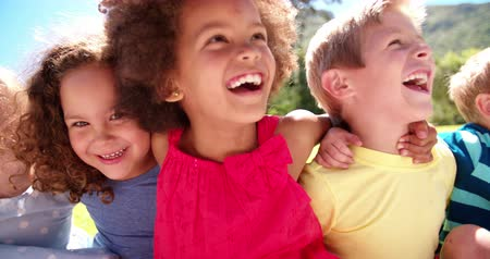 смеющийся : Happy mixed racial group of friendly children sitting in the sun laughing together Panning in Slow Motion Стоковые видеозаписи