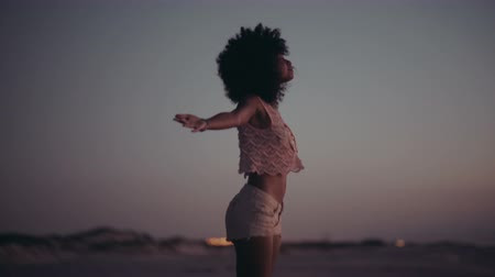 gülümseyen : African american girl with afro haircut standing with arms wide spread enjoying the sunset
