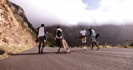 longboarder : Rear view slow motion video of a group of teenage skater friends walking on mountain road with longboards together in Slow Motion