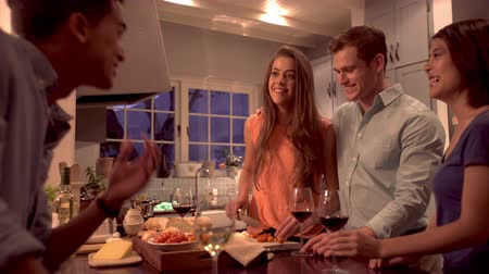 Happy mixed race couple friends laughing together in a kitchen while preparing dinner together