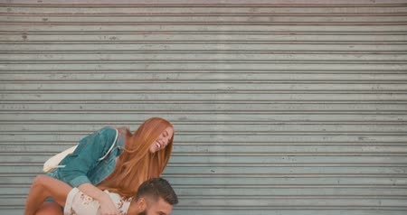 tatuagem : Laughing Hipster man carrying happy girlfriend piggyback in slow motion