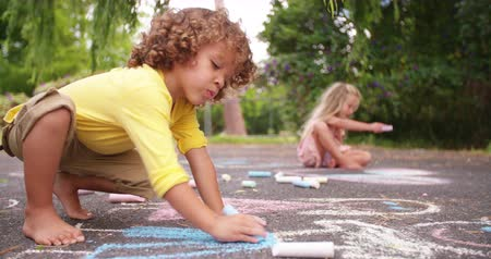 malarstwo : Little mixed race boy happily drawing chalk pictures on the tarmac walkway in a park Wideo