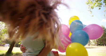 jovem : Happy little girl and her mom spinning together in a sunny park with balloons in slow motion Stock Footage