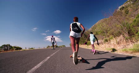 longboarder : African American skater girl downhill racing with friends on her longboard  in Slow Motion