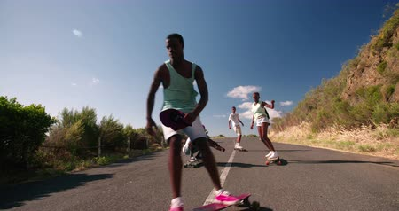 longboarder : Mixed group of teenaged skateboarders racing each other downhill on a deserted road in Slow Motion