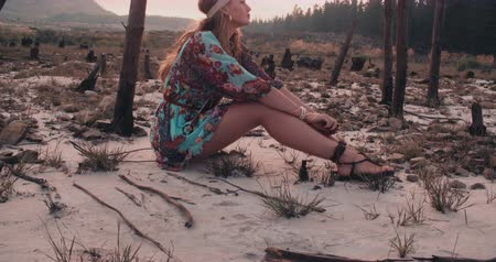 hippi : Full body shot of a boho girl in a floral dress sitting in a natural landscape in Slow Motion