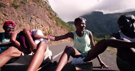 longboarder : Group of teenage longboarders of differing races sitting happily together on a road