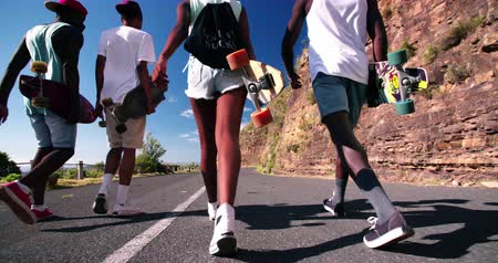 longboard : Cropped shot of cool teenage longboarders walking along next to each other on a road