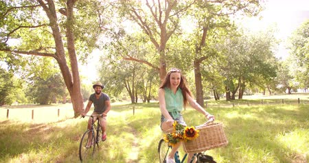 bisiklete binme : Happy young hipster couple cycling in summer together  in a park in Slow Motion Panning Stok Video