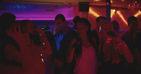 dança : Friends toasting and holding beer high at a party on dance floor