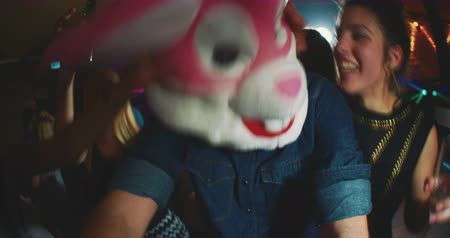 hipster : Group of friends at a party with one wearing a plush rabbit head