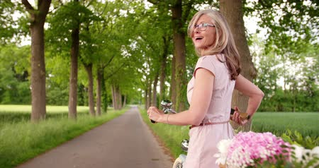 amadurecer : Portrait of a smiling mature woman looking back at the camera while enjoying a ride in a park on her classic bicycle in Slow Motion