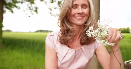 amadurecer : beautiful mature woman smelling some delicate flowers while standing with her bicycle in a summer park Stock Footage
