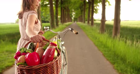 organic : Cropped image of a woman walking on a road in a park with her bicycle and a basket of organic vegetables fresh from the market