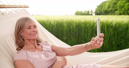 amadurecer : Mature woman smiling confidently while taking a self-portrait on her phone in a park while lying in a hammock