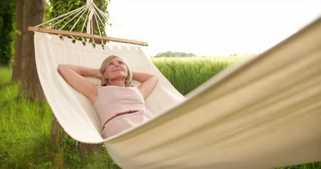 гамак : Relaxed mature woman lying in a hammock outdoors in a park and daydreaming  in Slow Motion
