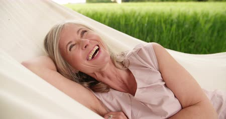 amadurecer : Portrait of a beautiful mature woman smiling happily while realxing in a hammock in a park