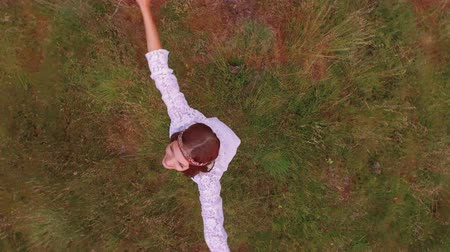 Çingene : Girl spinning on green grass as camera rotates from an aerial view Stok Video