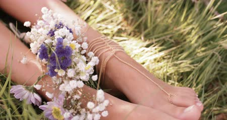 Çingene : Cropped overhead shot of a girls feet resting in lush green grass with fresh flowers and delicate foot jewellery Stok Video