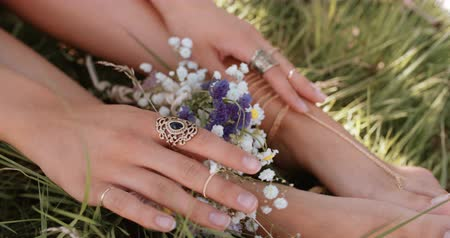 çevre : Cropped shot of a girls hands resting on her ankles with her feet resting in lush green grass decorated with wild flowers and gold chain foot jewellery Stok Video