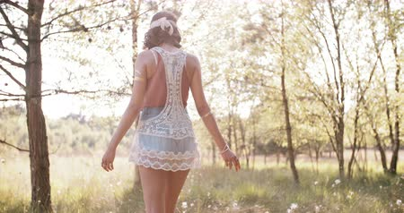 Çingene : Rearview shot of a boho girl wearing a vintage lace top walking through a summer park with her arms out feeling free