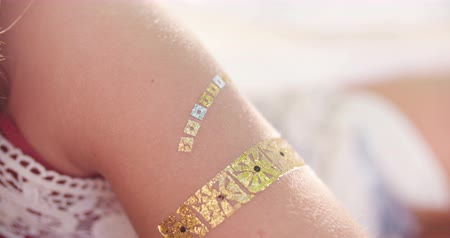 Çingene : Cropped closeup of a girl in boho styled clothes with a temporary gold foil tattoo on her arm