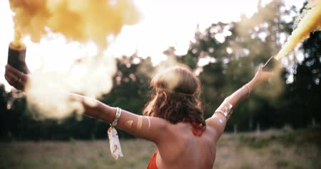 Çingene : Boho girl walking in field carrying smoke flares releasing clouds of yellow smoke