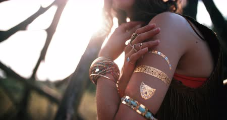 hippi : Cropped shot of a boho style girl sitting outdoors wearing many bangles and rings, Panning in Slow Motion Stock mozgókép