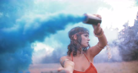 Çingene : Boho girl turning her arms with blue smoke flares in nature in Slow Motion