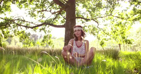 Çingene : Hippie girl sitting cross-legged in lush green grass under trees in a sunlit summer park