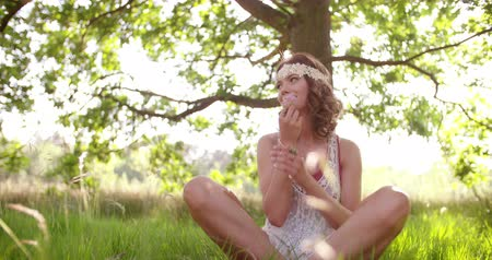 hippie : Smiling hippie girl sitting cross-legged in a lush green grass in a summer park smelling a pink flower Stock Footage