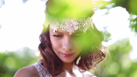 hippie : Dreamy hippie girl in a vintage white lace headband holding a small bouquet of wild flowers standing in nature looking away thoughtfully