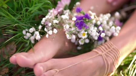 Cropped shot of a girls hands resting on her ankles with her feet resting in lush green grass decorated with wild flowers and gold chain foot jewellery Стоковые видеозаписи