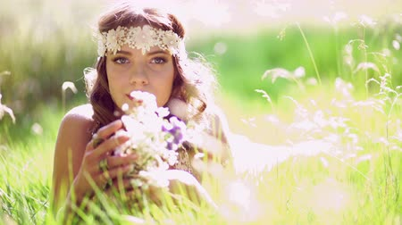 Çingene : Beautiful hippie girl lying in green grass in a summer park holding some fresh wild flowers and wearing a vintage white lace headband with gentle sun flare