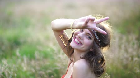 Beautiful hippie girl smiling up at the camera while lying in a field of wild grass using her hand to show a peace sign