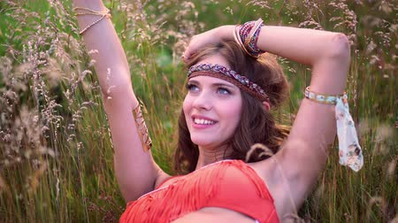 hippie : Boho fashion girl smiling while lying in a field of wild grass