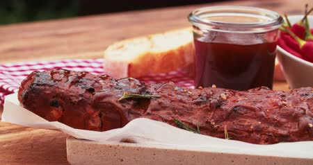 costela : Barbecued tender rack of ribs sprinkled with rosemary alongside barbecue sauce and a bowl of red chillies on a vintage wooden table Stock Footage