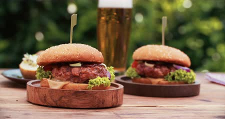 delicioso : Delicious home made gourmet cheese burgers made from healthy prime beef with fresh ingredients placed on wooden platters on a rustic wooden table with a tall glass of beer in the background outdoors at a back yard barbecue