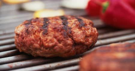 faszén : High quality fresh beef patties grilling outdoors on a barbecue with glowing coals and a little flame in Slow Motion