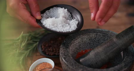condimento : Hands adding a pinch of salt into a dark stone mortar and pestle to show how to make a delicious dry seasoning for meat with other spices and herbs around on the wooden table